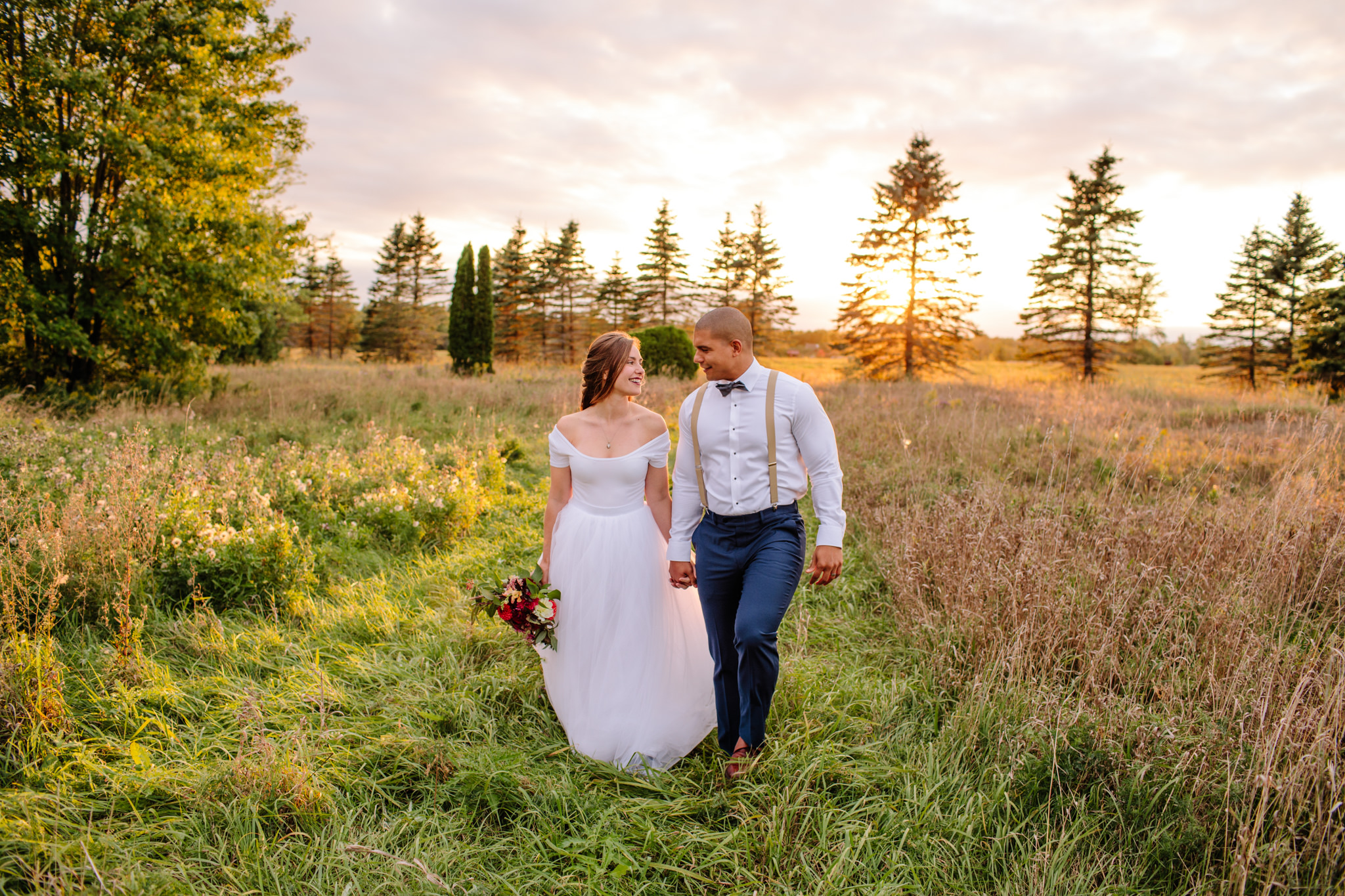 bride and groom in a field celebrating their lindsay wedding