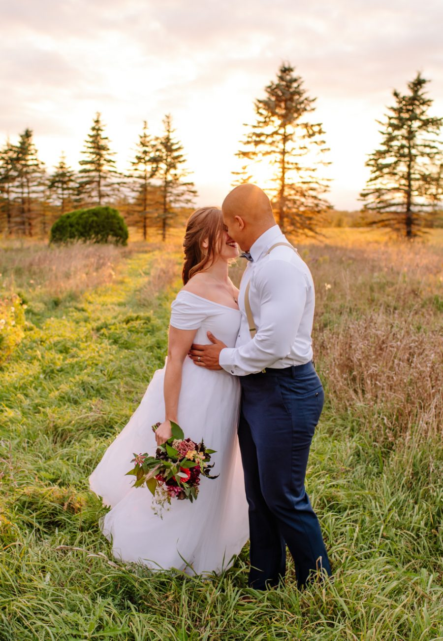 sunset in a field with a bride and groom kissing after lindsay wedding