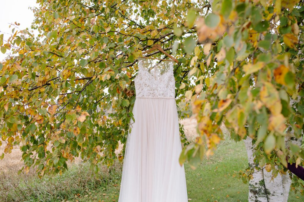 wedding dress hanging in birch trees during getting ready of wedding day