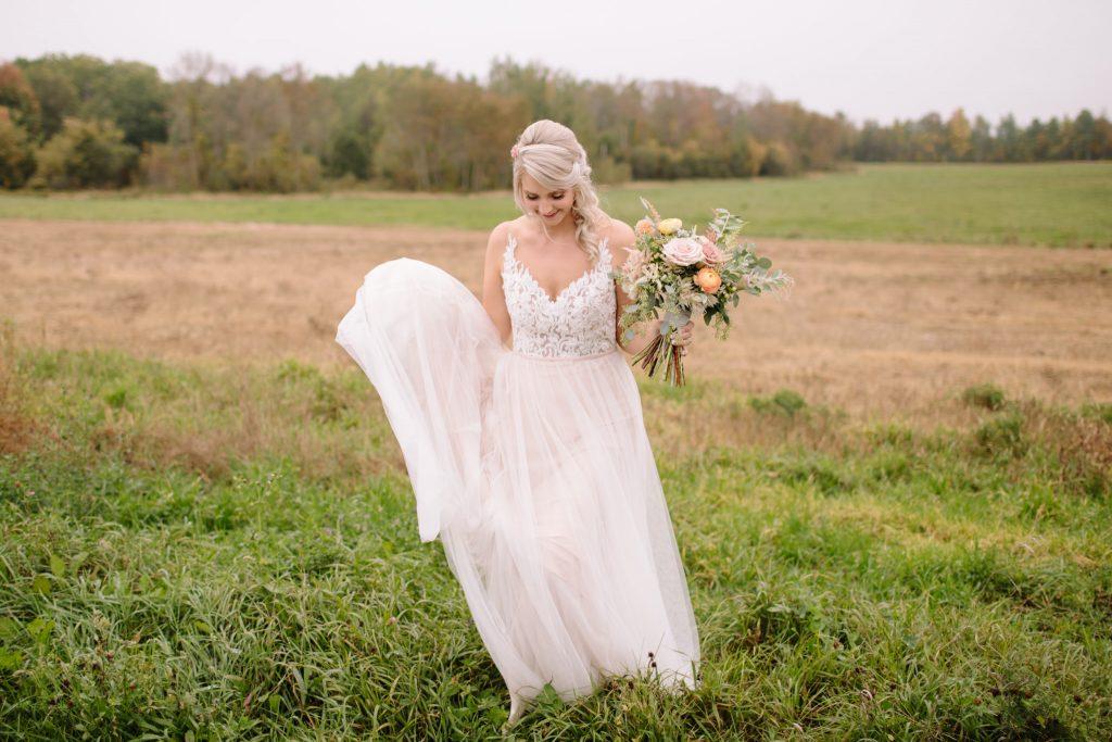 bride walking through field with boquet