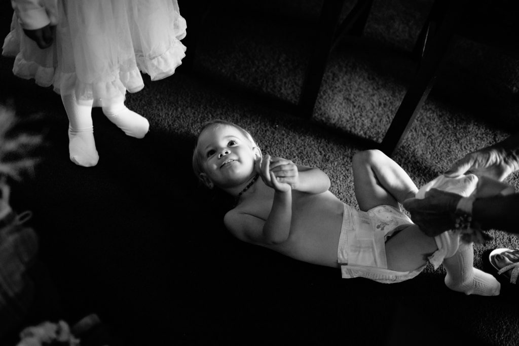 child laying on floor getting dress for wedding by parent
