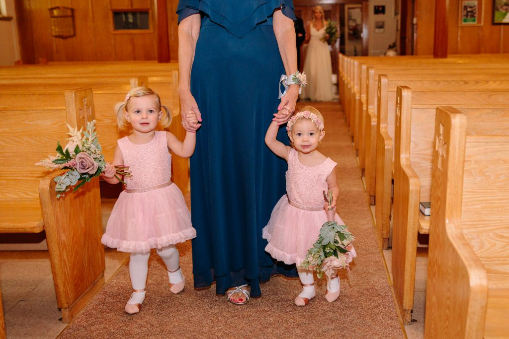 flower girls being walked down aisle on wedding day
