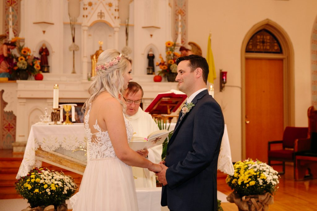 groom smiling at bride during wedding ceremony in catholic church