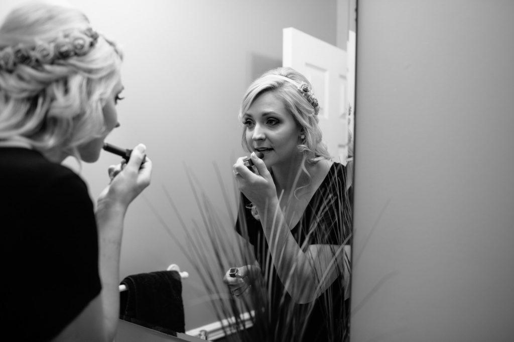bride getting ready on her wedding day applying lipstick in bathroom mirror