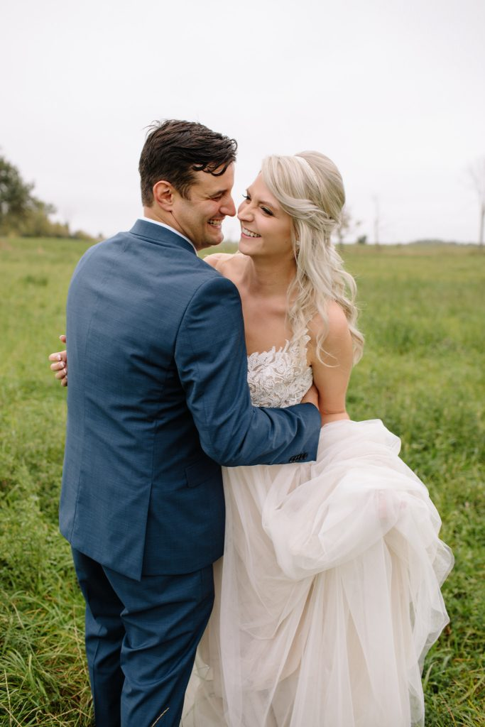bride and groom embracing each other while standing in a field for wedding portraits during outdoor barn wedding