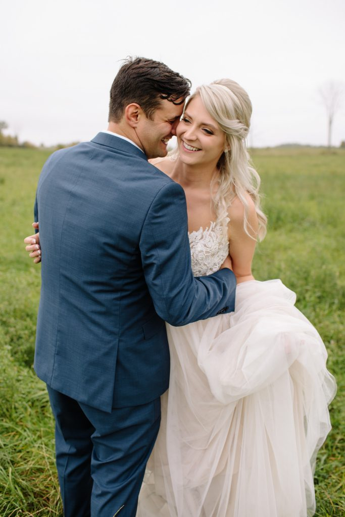 groom and bride embracing each other in field laughing and smiling