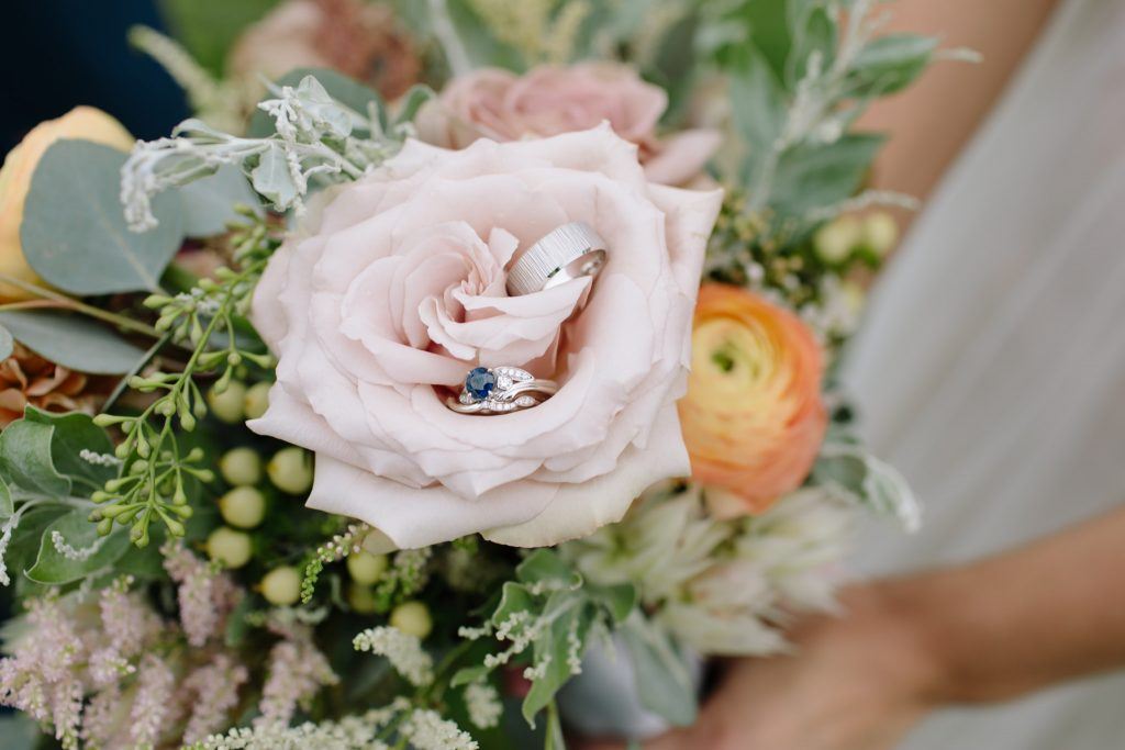detail shot of flowers and wedding rings