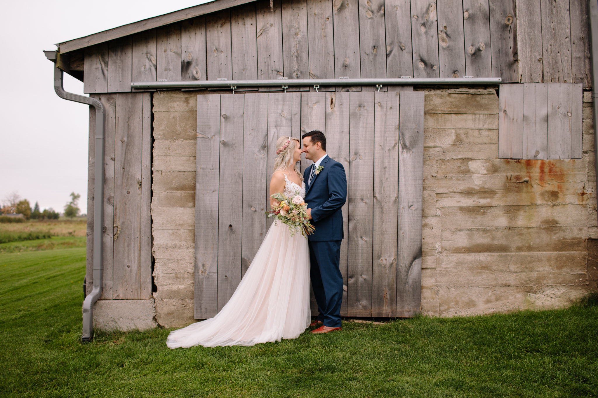 bride and groom smiling while standing infront of a rustic barn door