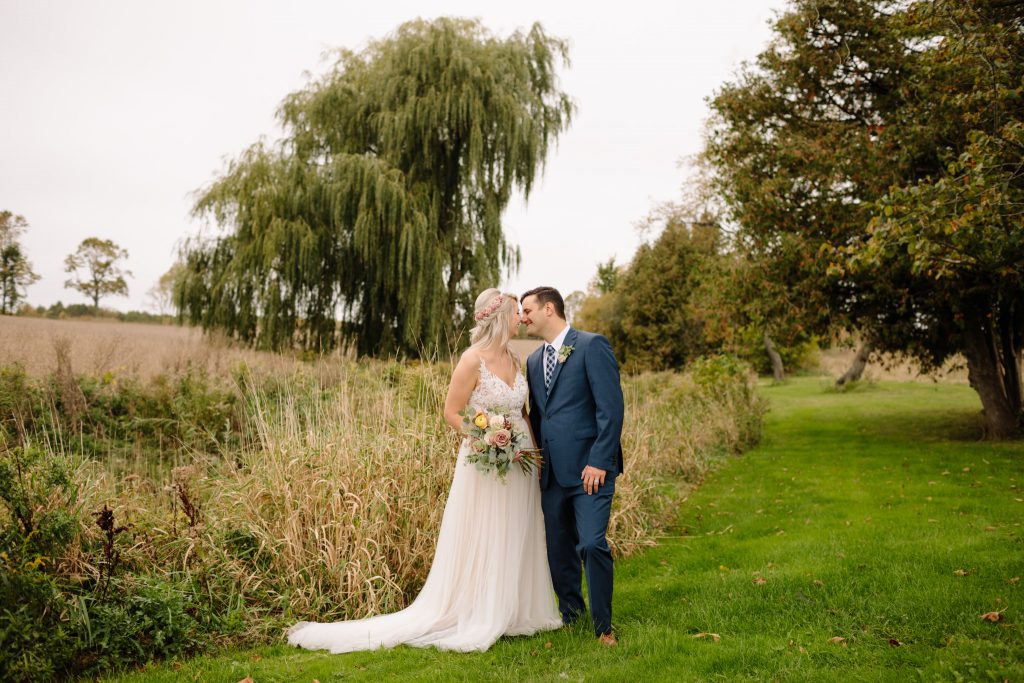 bride and groom kissing infront of a weeping willow tree