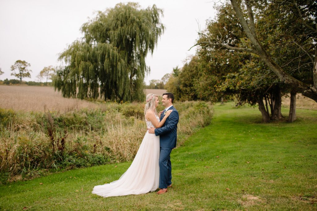 bride and groom looking into each others eyes smiling infront of a weeping willow tree