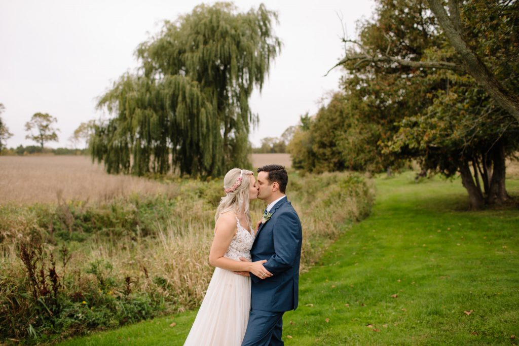 bride and groom kissing in a field during their wedding day