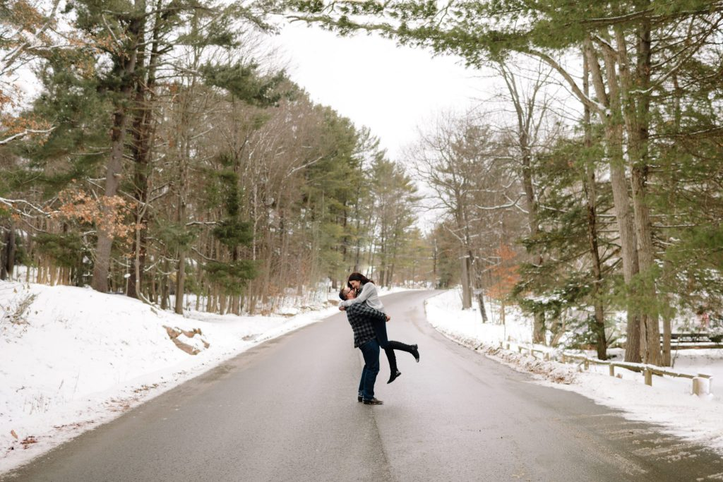 Engaged couple embracing each other on a snowy road in the country