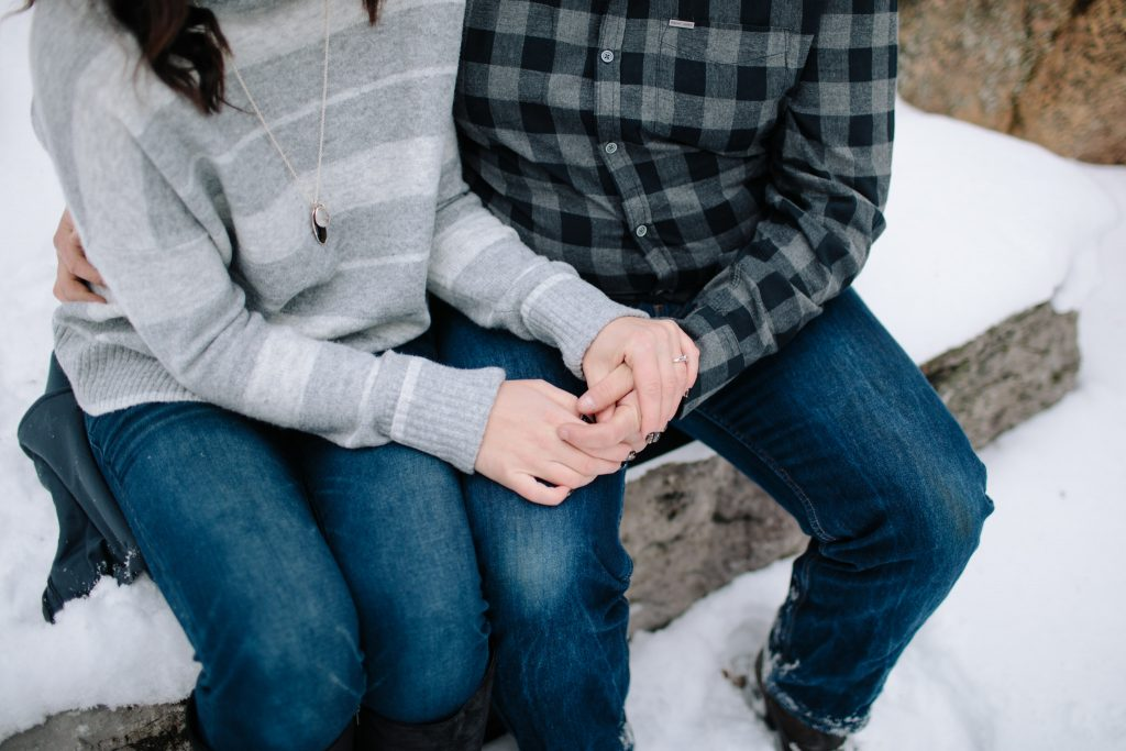 hand detail shot of engaged couple while sitting in the forest