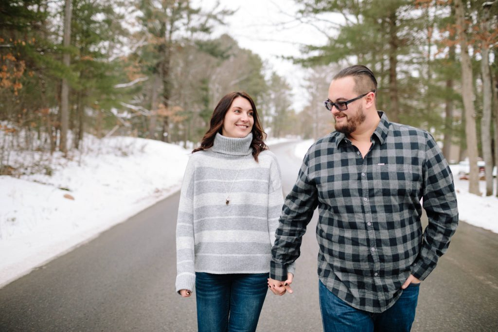 girl and guy walking down road during their snowy engagement session holding hands