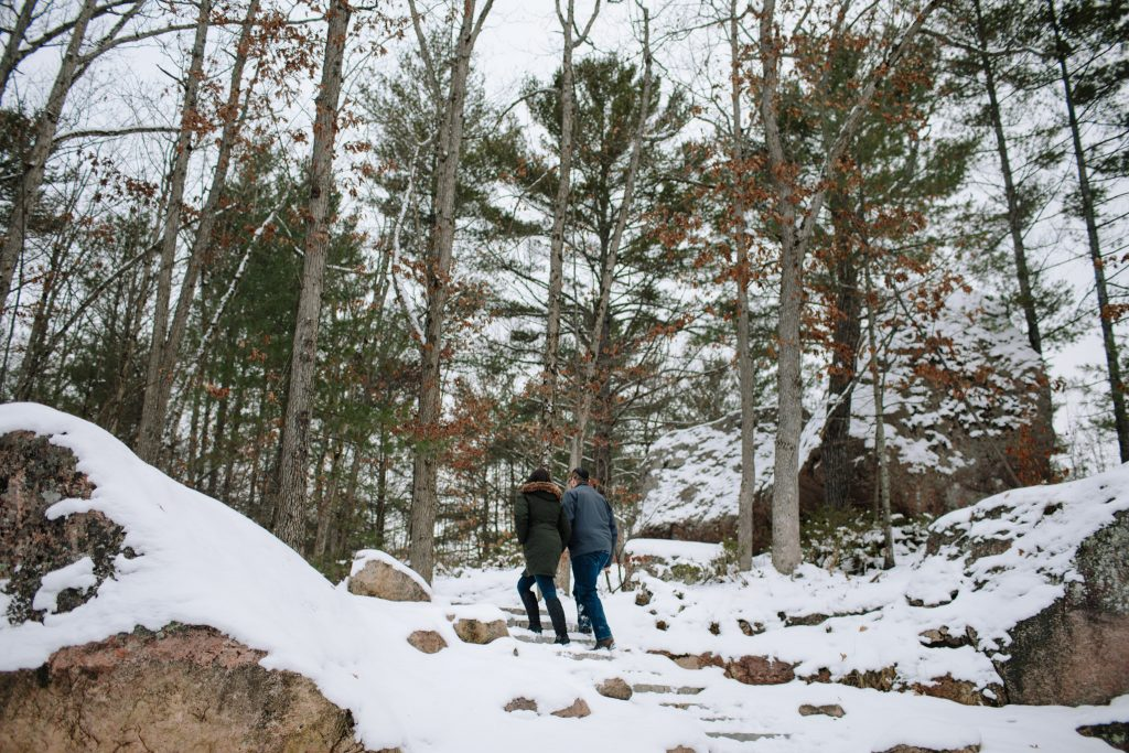 couple holding hands while walking up the snowy steps at Adam and Eve Rock in Buckhorn ON