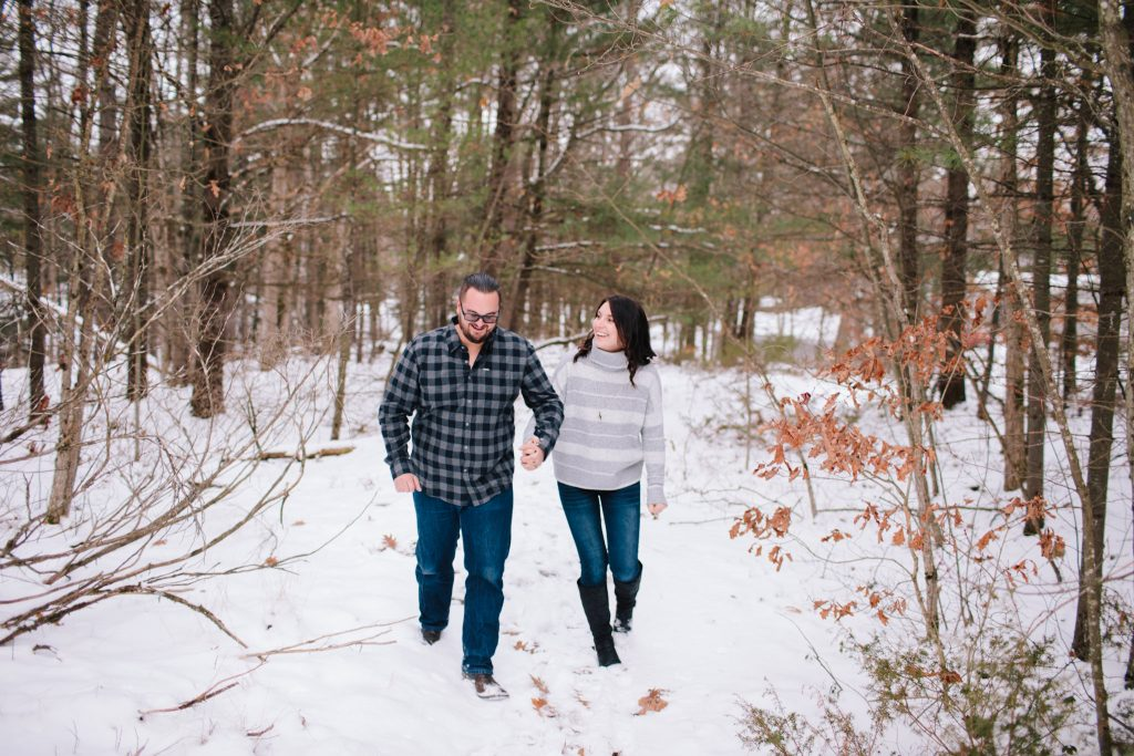 couple walking through snowy woods during their winter engagement session