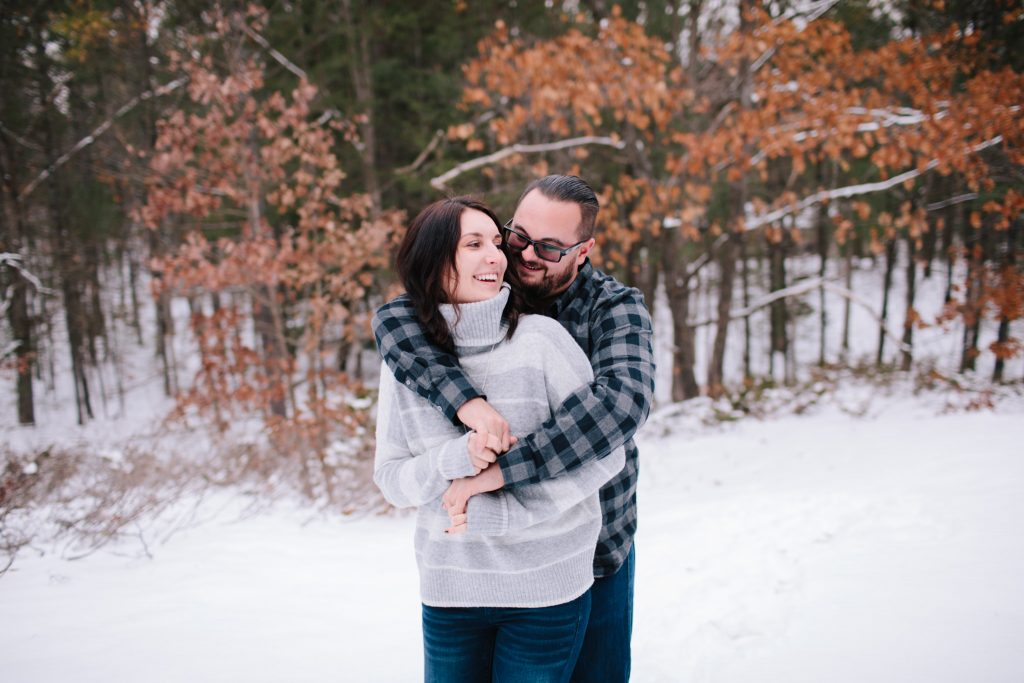 engaged couple in an embrace laughing with arms around each other