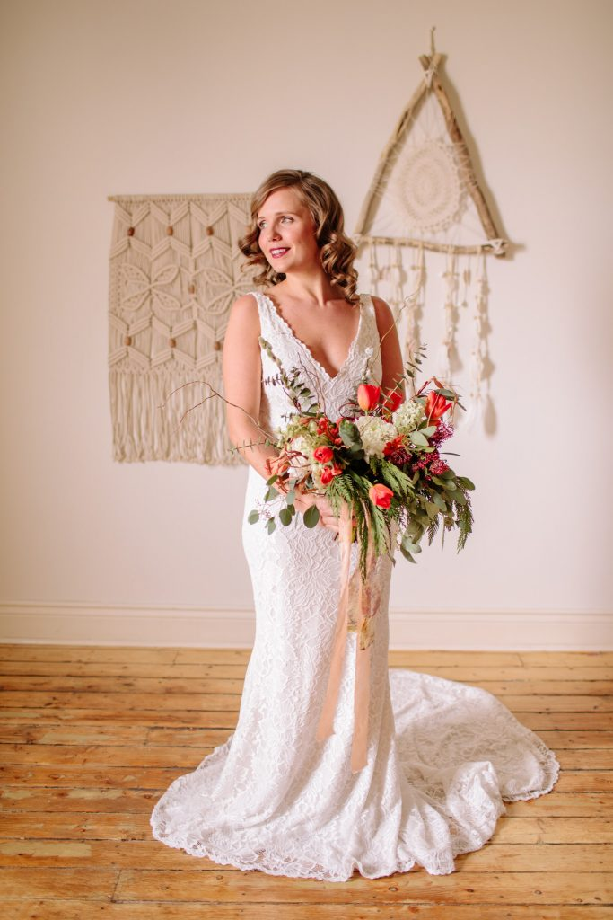 bride wearing lace dress holding bouquet