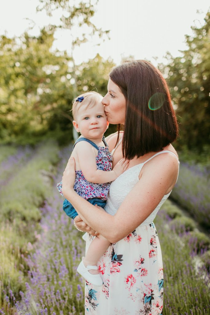 mother cuddling her toddler during sunset at durham lavender fields