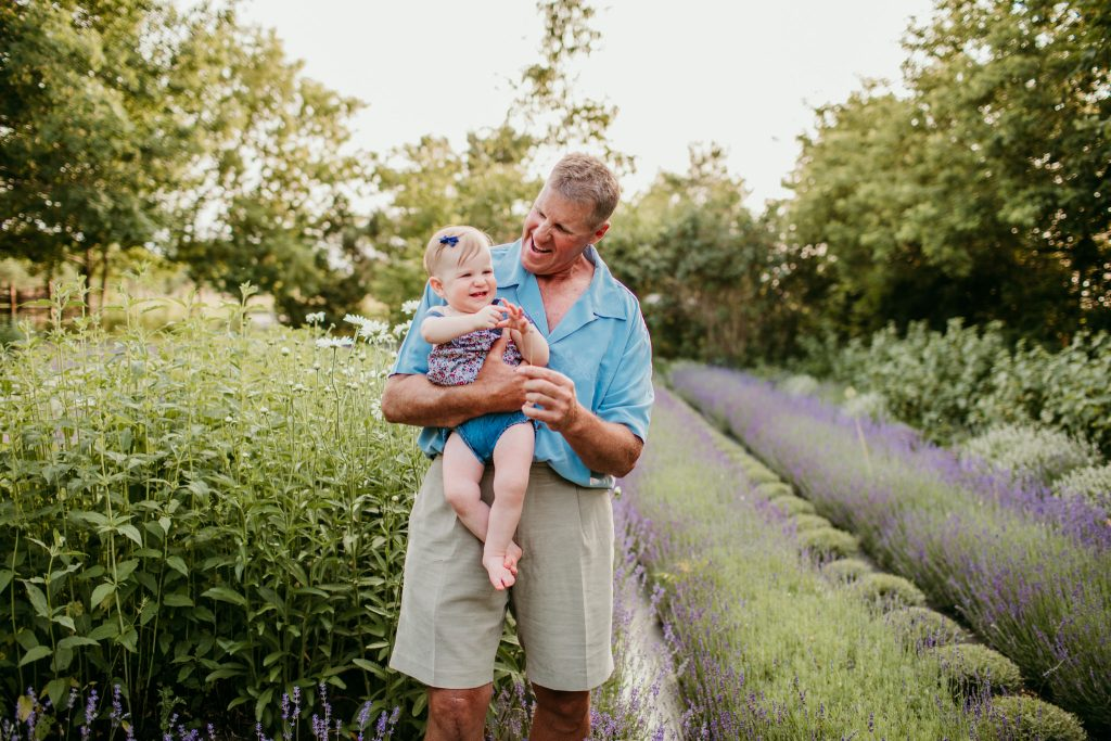 grandfather looking down and smiling at granddaughter during their photo session in a treed field at sunset