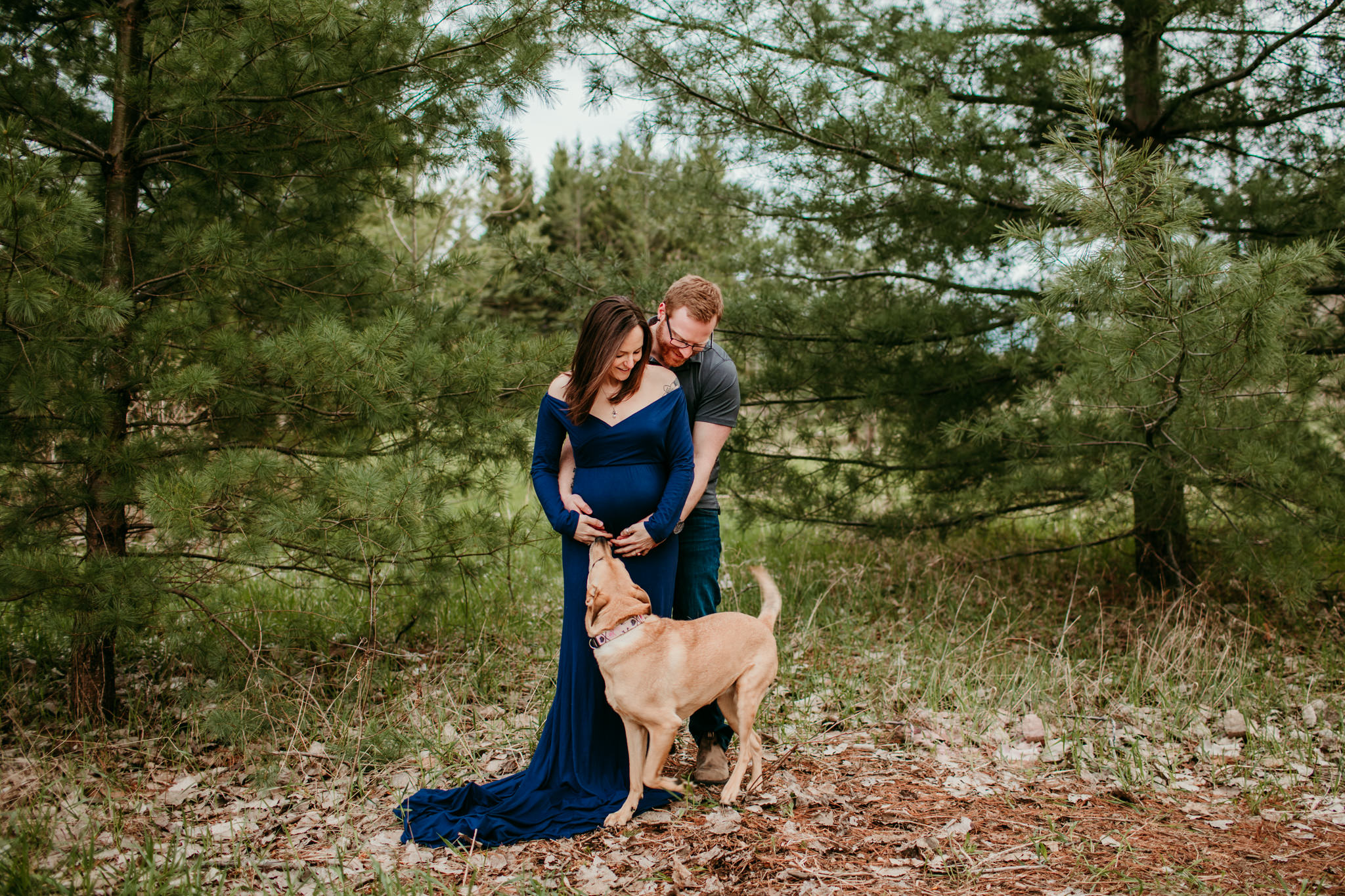 girl holding her bump while her dog kisses her stomach