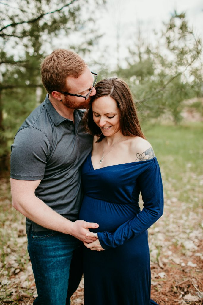 guy and girl cuddling during a moment in their maternity photo shoot