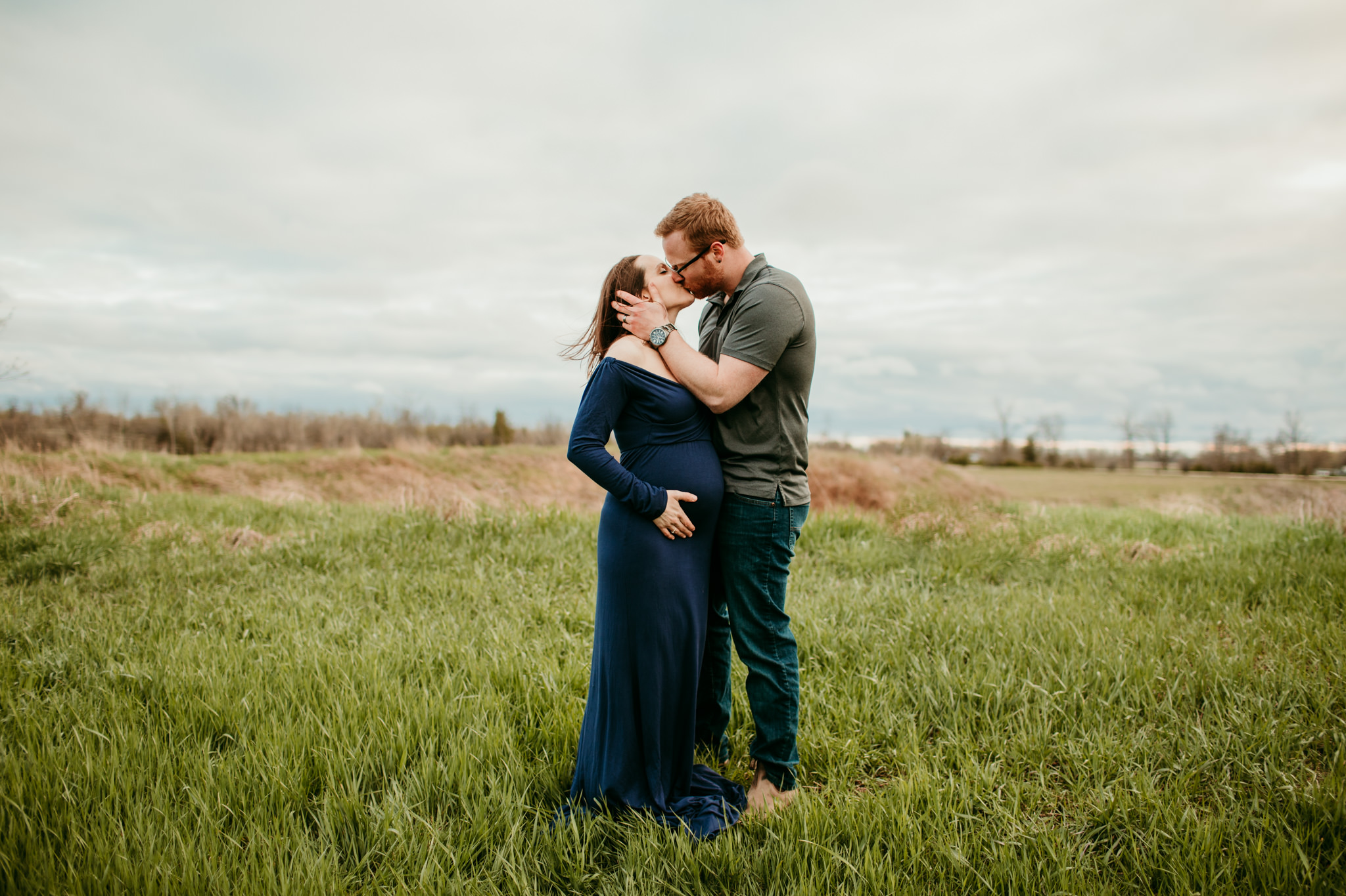 pregnant woman kissing her husband in the wind outside in a field