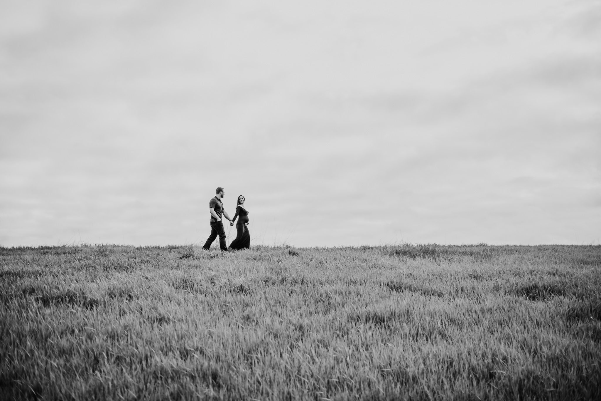 husband and wife walking on crest of hill while holding hands and pregnant