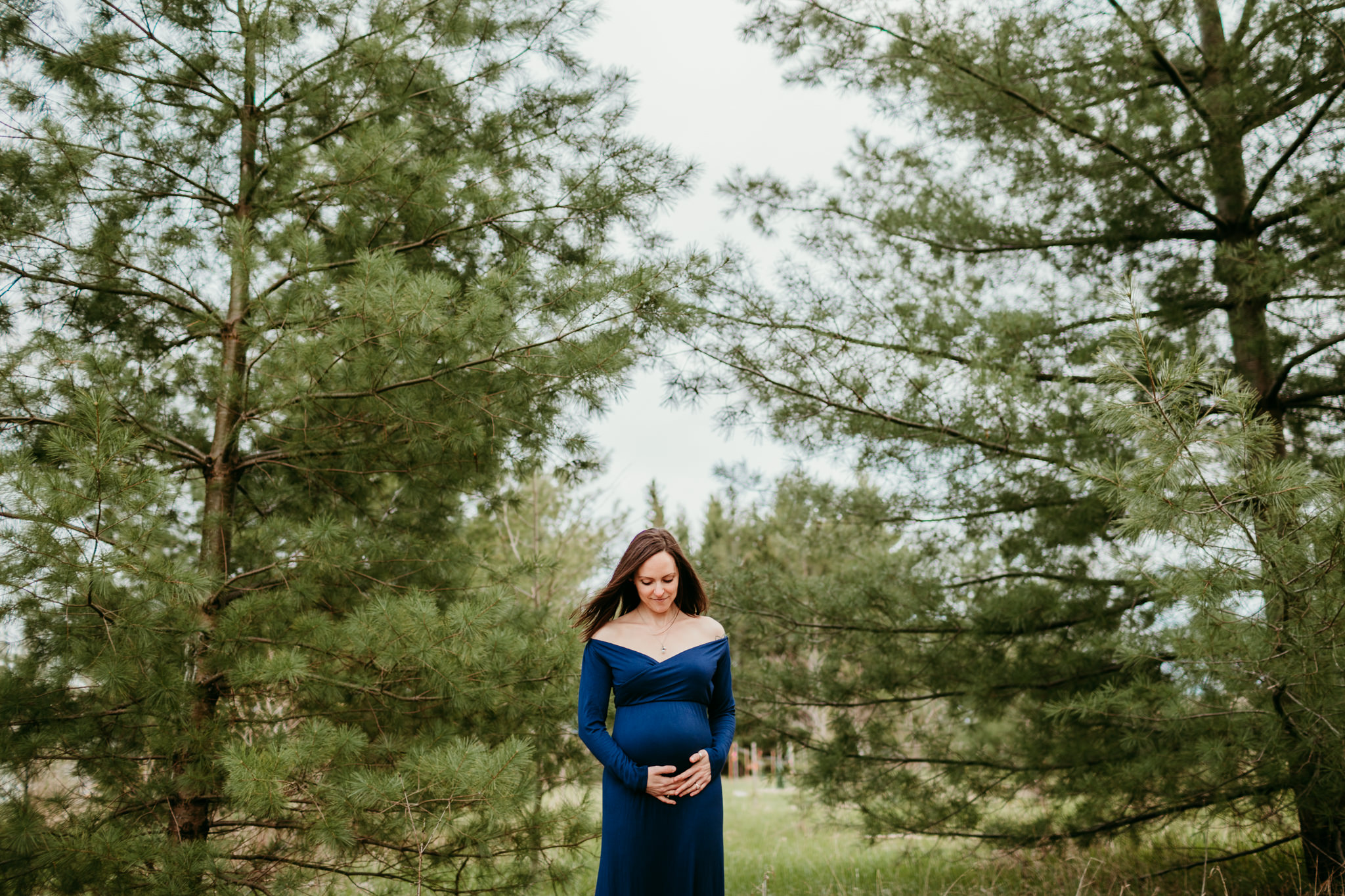 woman looking at her baby bump while standing in nature during her maternity photo session