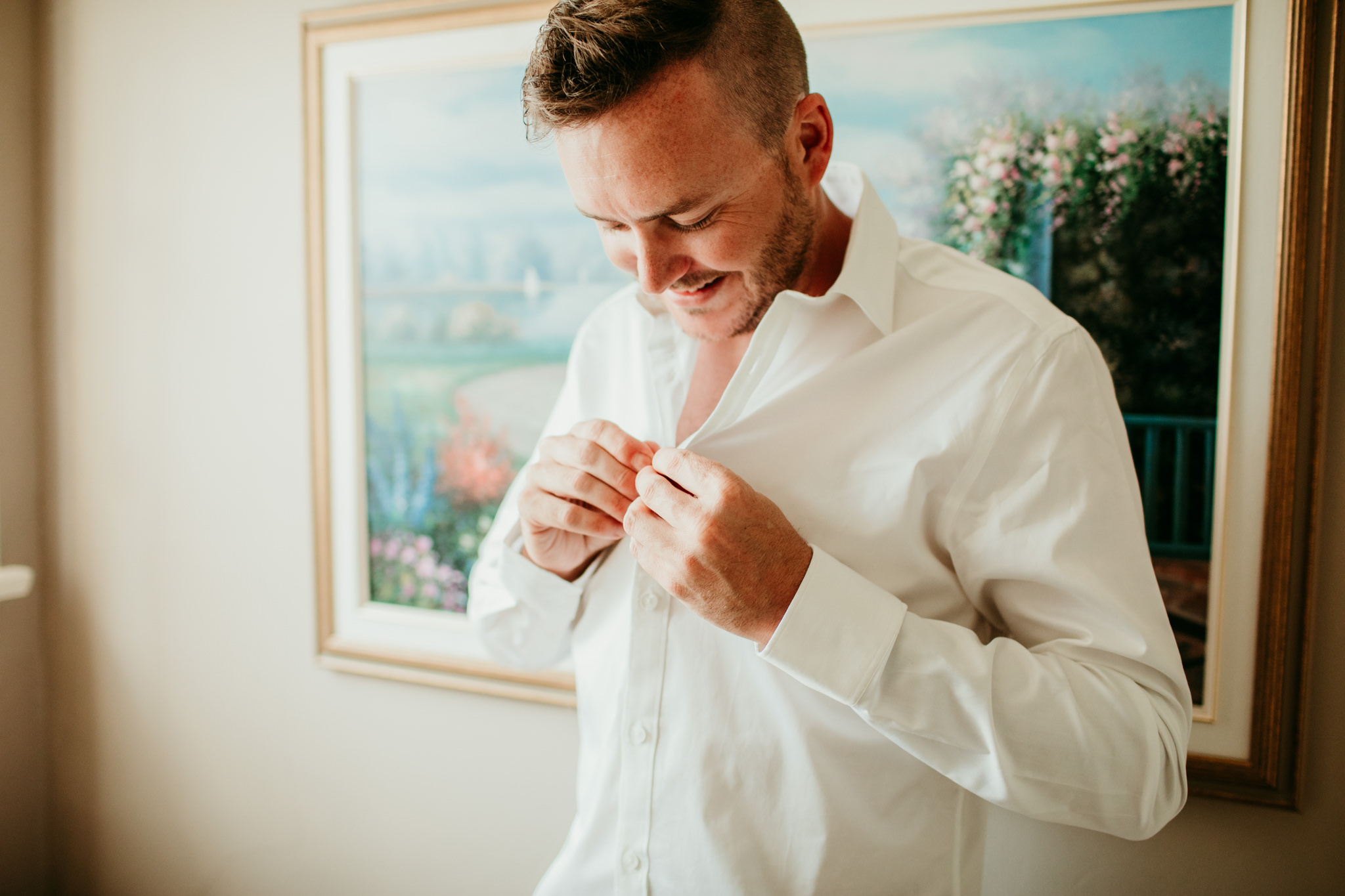 groom doing up top button on his shirt while getting prepared for his wedding ceremony