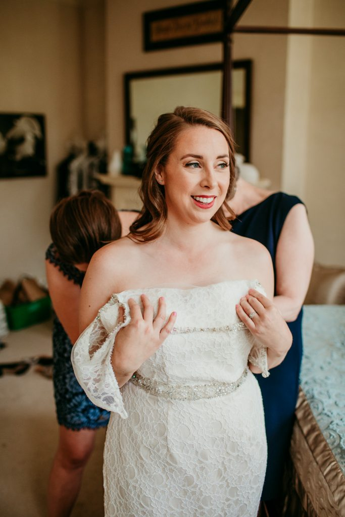 bride smiling while putting on her wedding dress