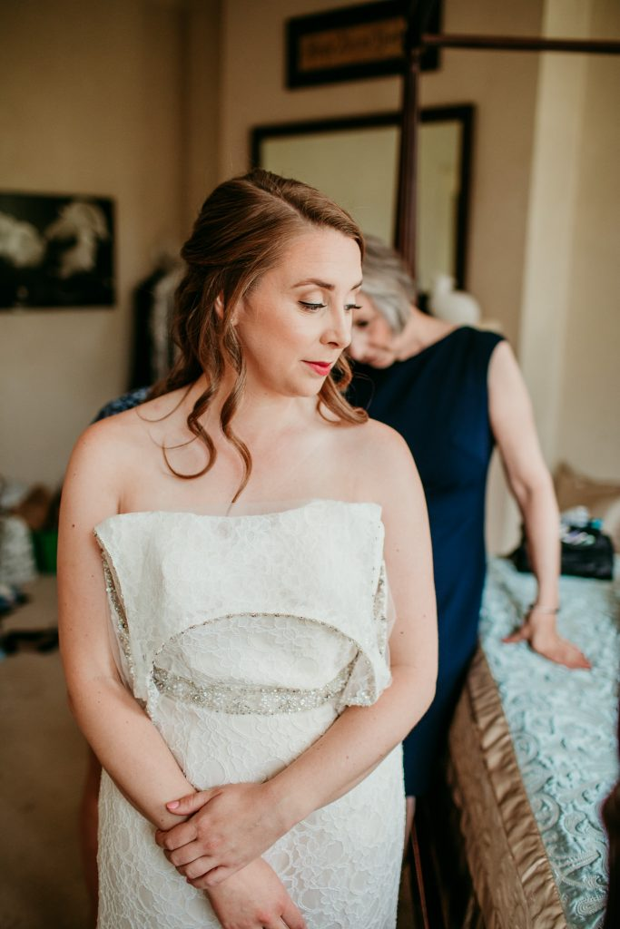 woman putting her wedding dress on looking down to the side with a serious face