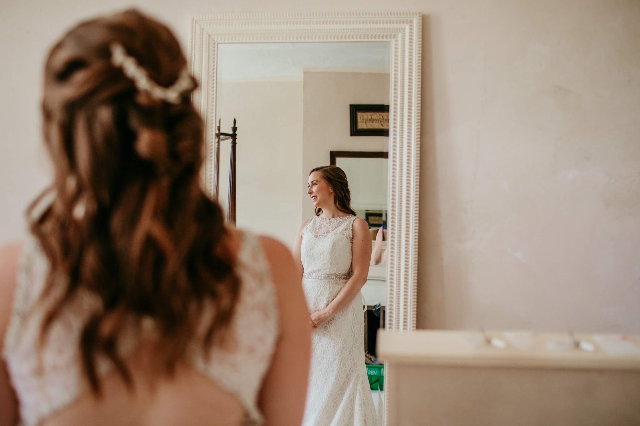 bride smiling to the side of the frame dressed in her wedding dress with reflection in the mirror