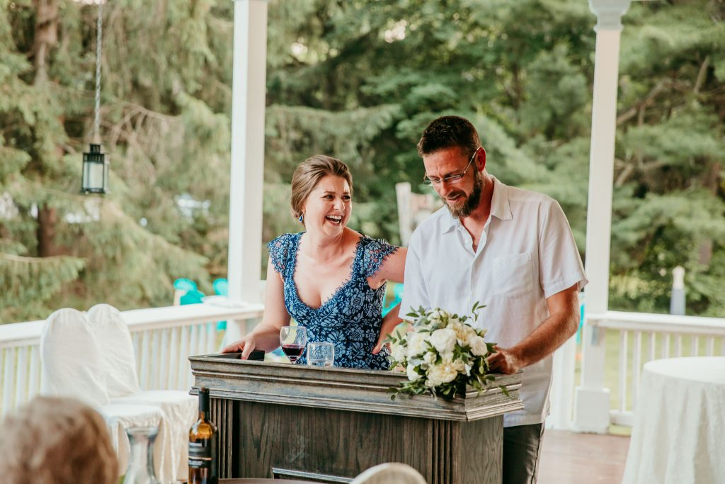 sister and brother giving speeches and laughing during wedding reception