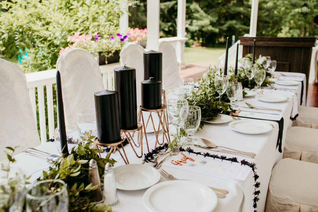 black and gold place setting for a wedding dinner amongst greenery
