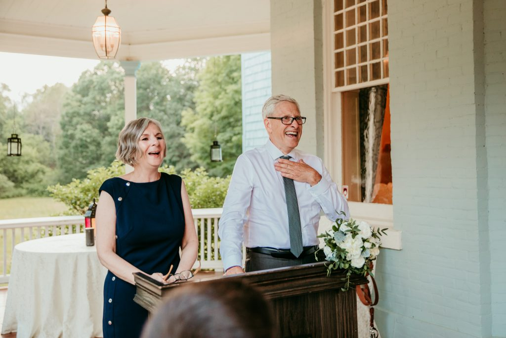 parents laughing at their speeches during the reception