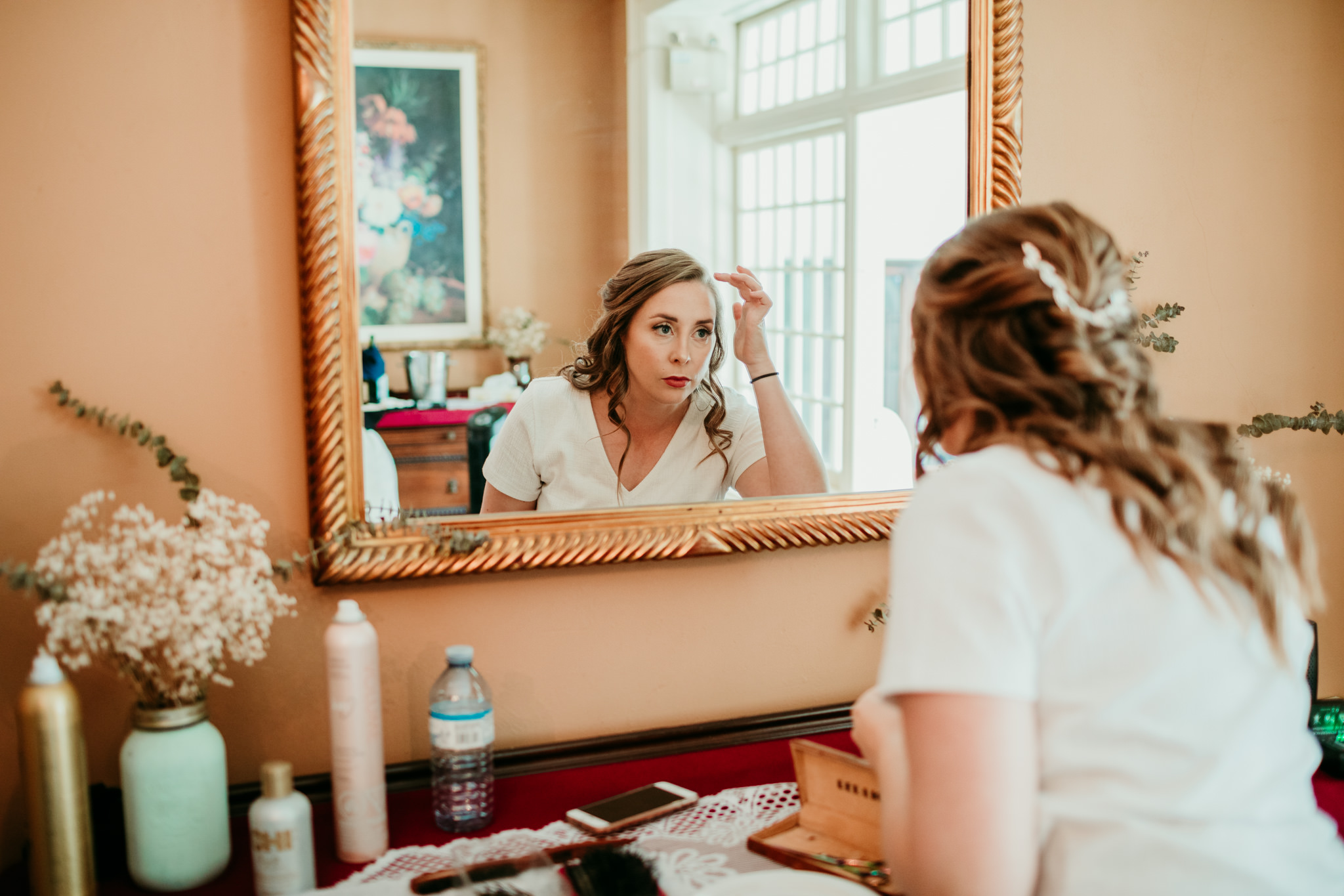 bride looking in the mirror at her hair