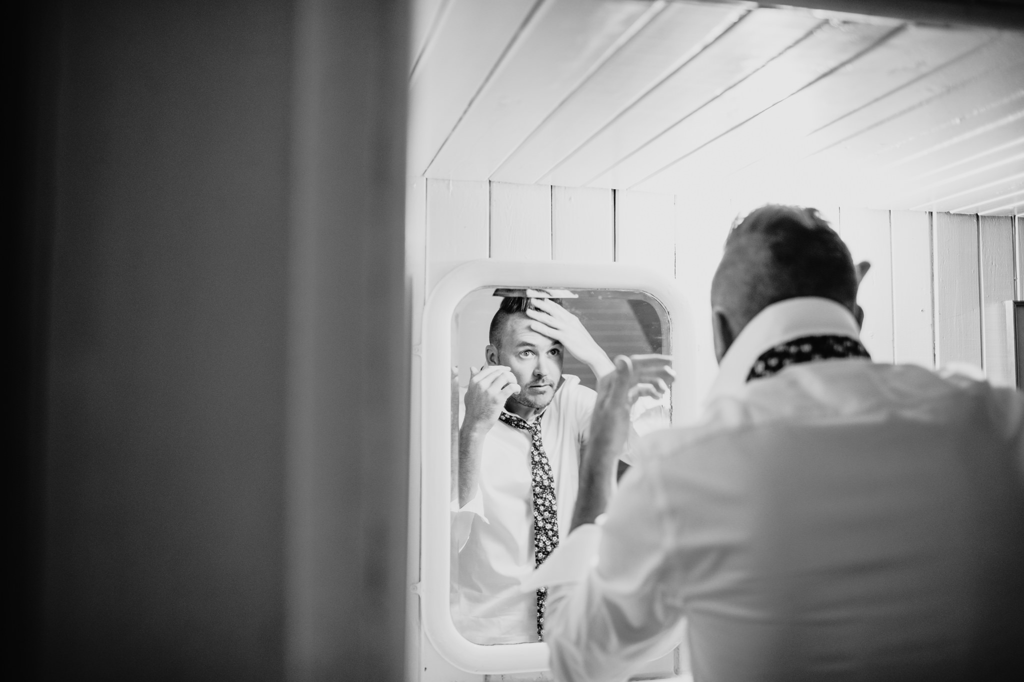 grooms reflection in the mirror while doing his hair