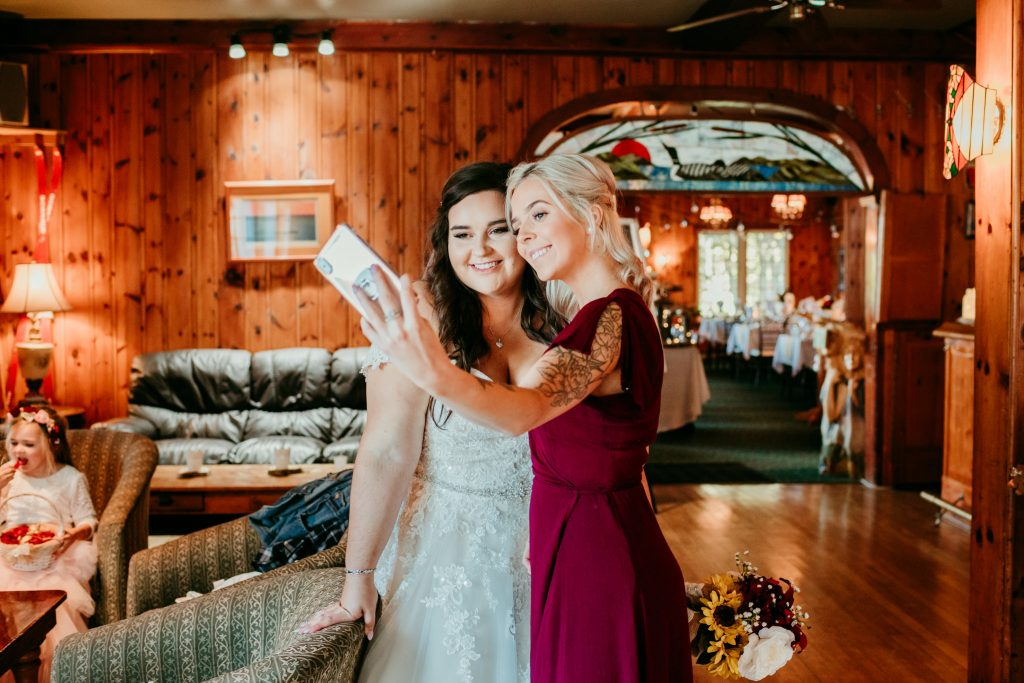 bridesmaid doing phone selfie with bride