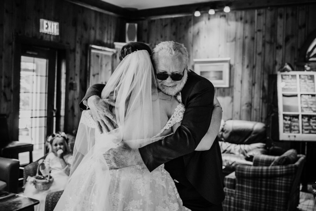 father hugging daughter before walking down the aisle