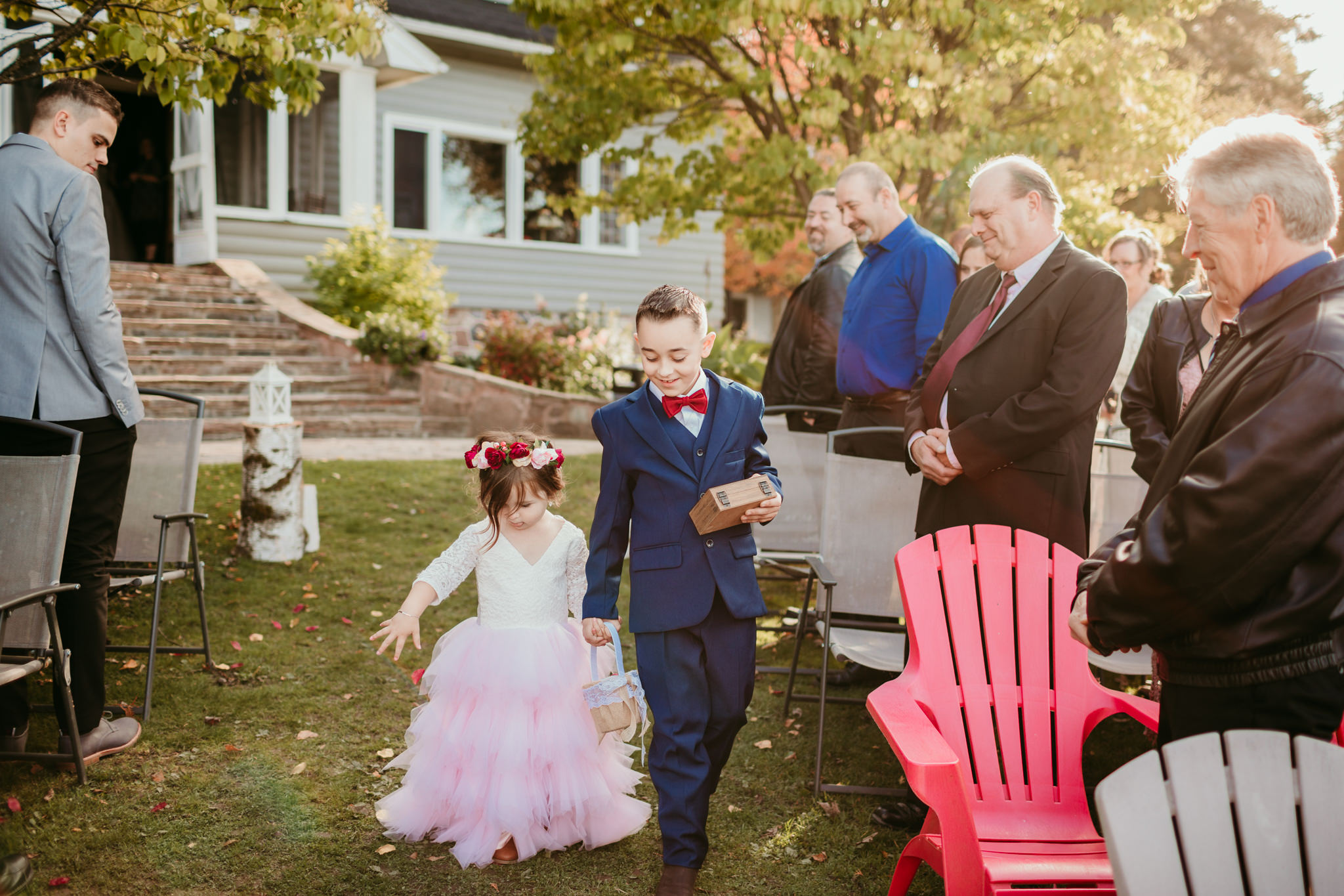 flower girl and ring bearer walking down outdoor aisle for wedding in haliburton