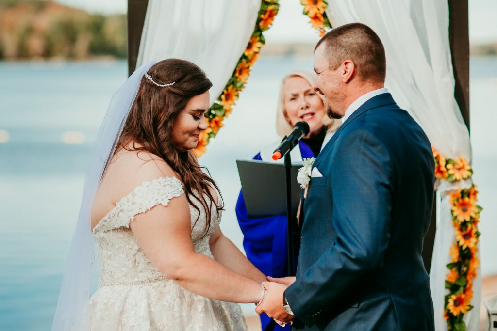 Bride and groom holding hands as they exchange vows
