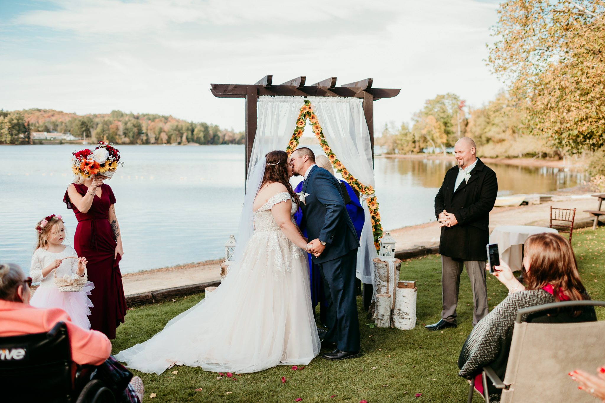 bride and groom kissing under wedding arch at their wedding in haliburton