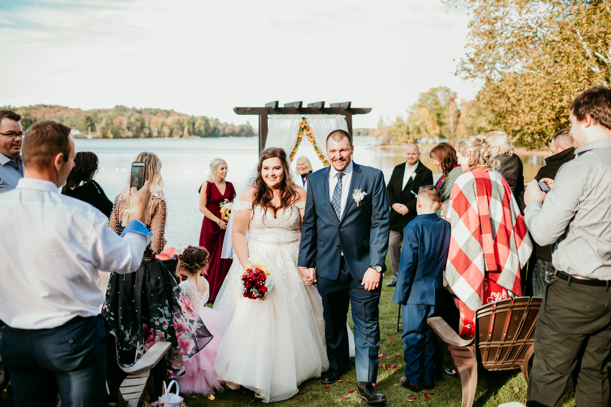 bride and groom walking down the aisle outdoors in fall at lakeside ceremony