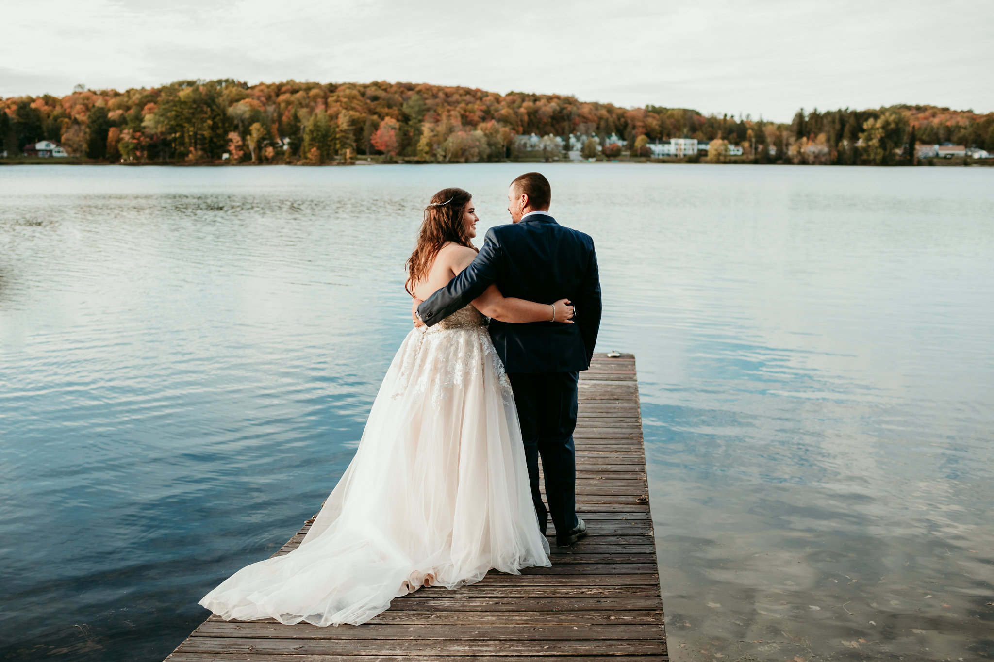 groom and bride hugging while standing on a dock looking out at lake