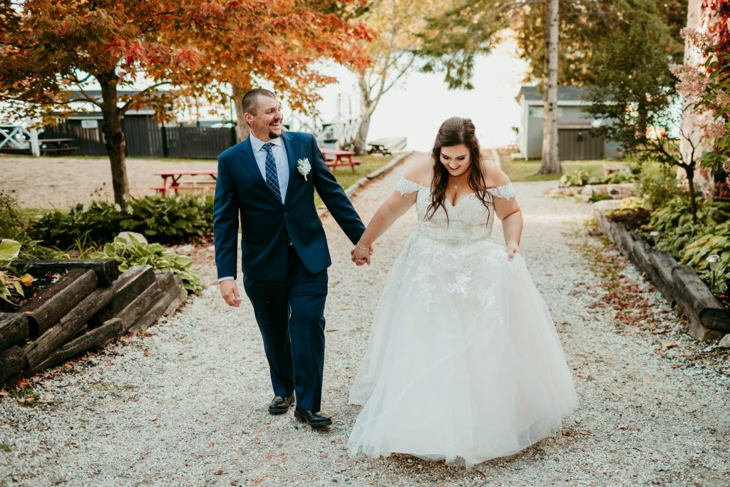 bride and groom holding hands walking up pathway