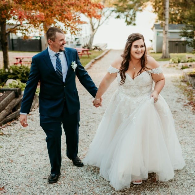 bride and groom holding hands laughing