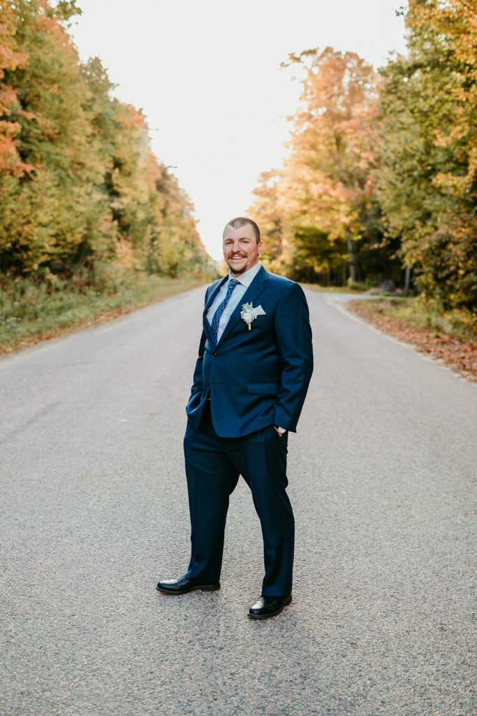 groom standing on road with fall trees in background smiling at camera