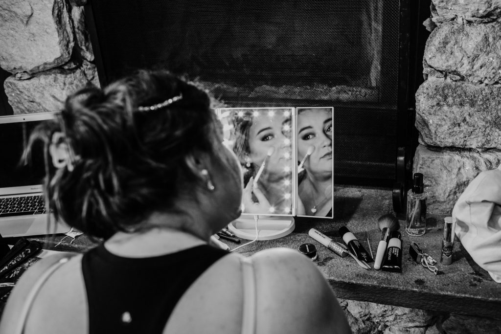 mirror reflection of girl doing makeup for her wedding in Haliburton