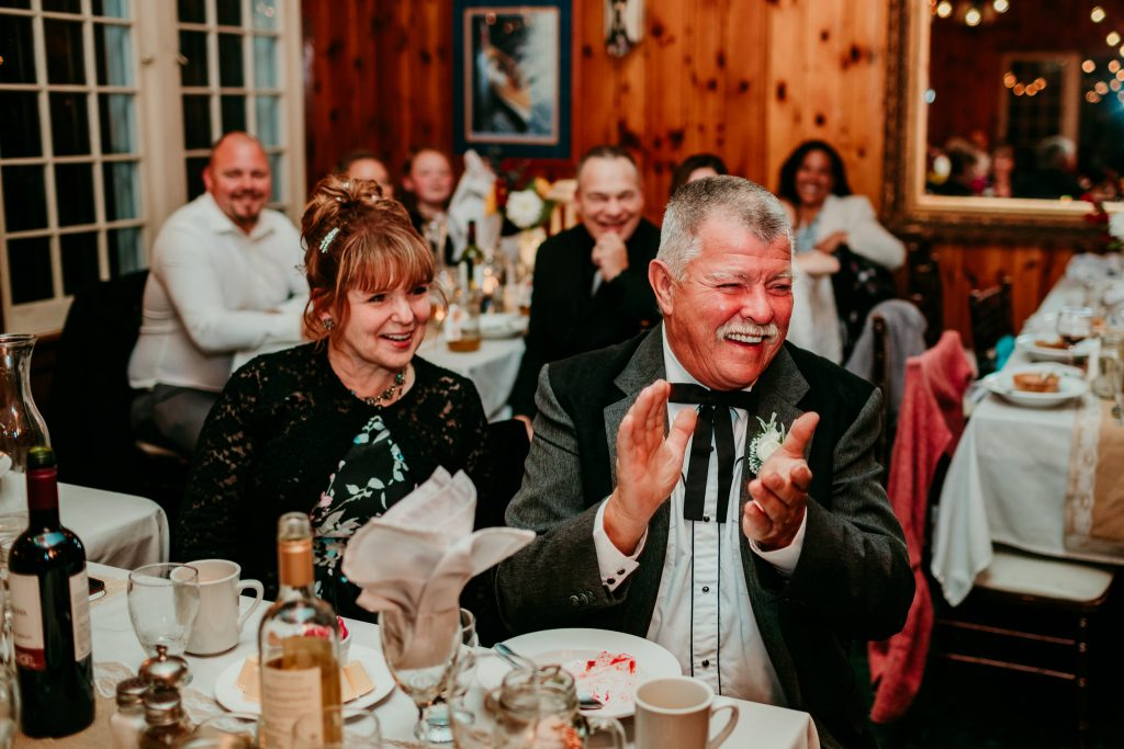 father and mother of groom laughing and clapping during reception
